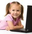 Cute little girl is sitting on floor with laptop