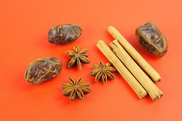 Christmas baking: Cinnamon, star anise, dates on red background