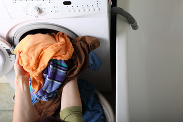 woman loading the washing machine in bathroom
