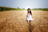 Happy free woman running in grain field