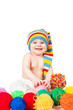 smiling baby in a hat plays with balls of yarn