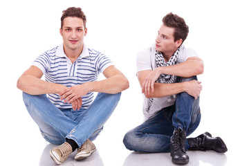 two casual men sitting on a white background