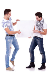 two young men holding a blank board