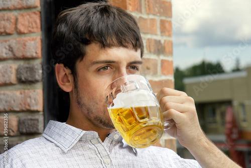Młody facet pije piwo
