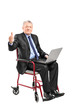 Mature businessman in a wheelchair working on a laptop and givin