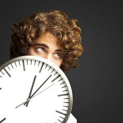 man hidden behind clock