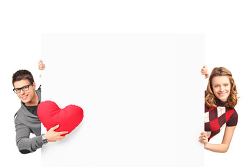 Smiling girl and boy with heart shaped pillow posing behind a wh