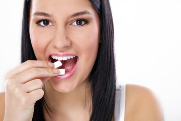 Beautiful girl taking white chewing gum, smiling