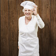 senior woman cook doing an excellent symbol against a wooden bac