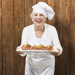 senior woman cook holding a tray with muffins against a wooden b