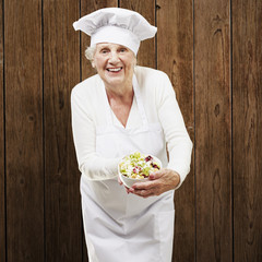 senior woman cook holding a bowl with salad against a wooden bac