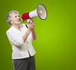 portrait of senior woman holding megaphone over green background