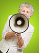 portrait of senior woman screaming with megaphone over green bac