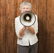 portrait of senior woman screaming with megaphone against a wood