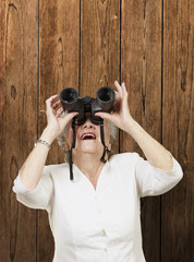 portrait of senior woman looking through a binoculars against a