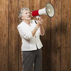 portrait of senior woman holding megaphone over wooden wall