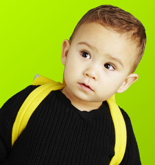 portrait of adorable kid carrying yellow backpack over green bac
