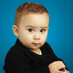 portrait of serious kid looking ahead over blue background