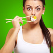 young woman covering her mouth with a sushi piece against a gree