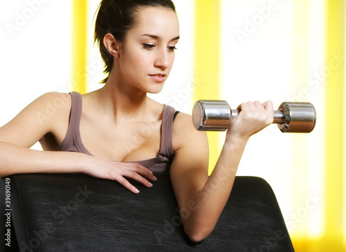 portrait of  young woman lifting free weights