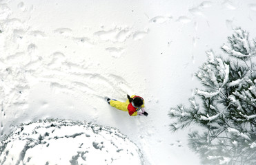 elevated view of girl playing on snow covered yard