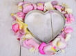 Heart made of rose petals on white wooden background