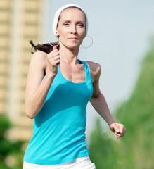 Beautiful woman running in green park