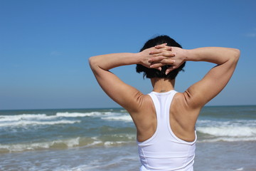 An athletic woman from the back, stretching at the beach