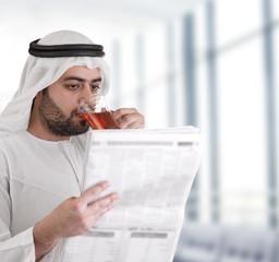 arabian business man drinking tea & reading news-