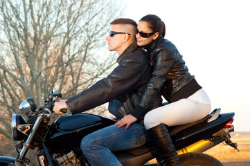 Young happy couple ready to go on a ride with motorcycle