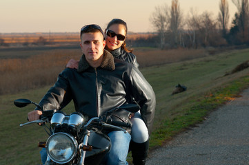 Young happy couple riding a motorcycle at sunset