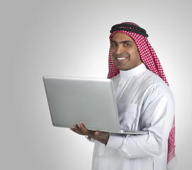 Arabian Businessman using laptop computer standing,