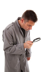 Man with raincoat is looking with magnifying glass