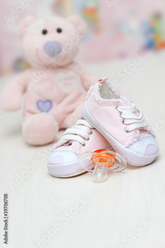 baby shoes and teddy bear toy on a wooden floor