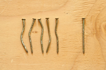 Conceptual image of crooked nails and straight nail