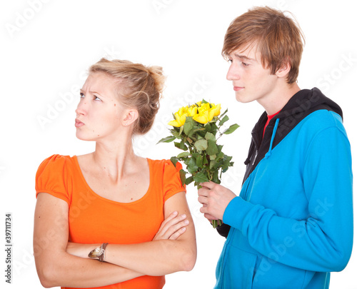 man offering flowers to his girlfriend after argument