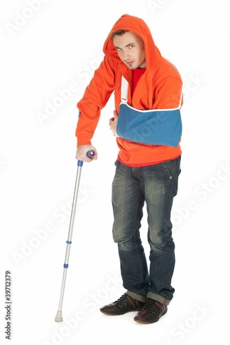 man with broken hand walking on crutc full length