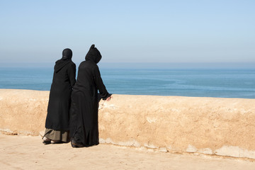 Moroccan women looking out over the ocean