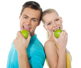 Young couple posing back to back with green apples