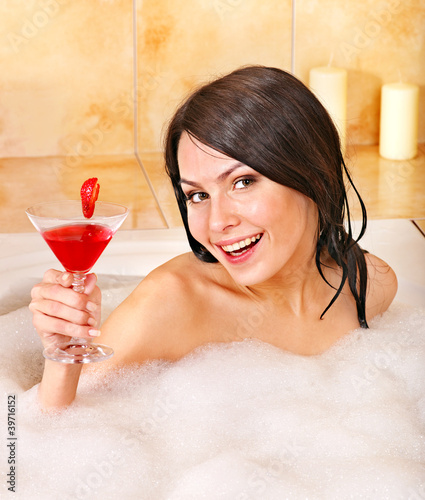 Woman washing in bubble bath.