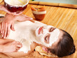 Girl having clay body mask apply by beautician.