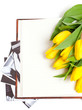yellow tulips lying on book with black and white photographs