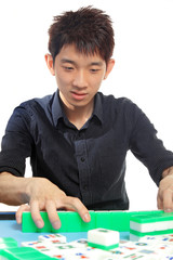 Chinese man play Mahjong, traditional China gamble.