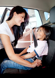 Mother helping to fasten seat belt