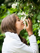 Beautiful young woman smelling white jasmin flowers