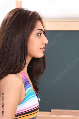 Young woman in classroom by blackboard