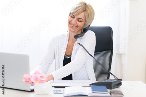 Senior business woman speaking phone and working on laptop