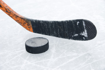ice hockey stick and puck on ice