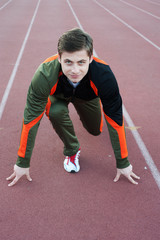 Young male athlete in ready position on running track