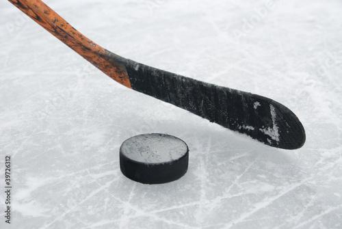 ice hockey stick and puck on ice
